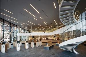 Die Schalterhalle von Henk Döll: eine Kaskade heller  Töne und Materialien, mit gebogenen randlosen Gläsern als Balustraden und einer imposanten Wendeltreppe nach oben; hell und leuchtend wie skandinavische Interieurs<br />