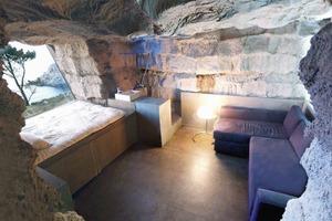Der Blick ins Innere zeigt Bett, Bad, Sitzecke. Der Kamin ist links, der Eingang im Rücken<br />