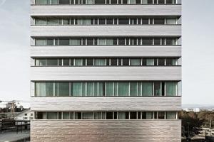 An der Fassade lässt sich grob das Raumprogramm der einzelnen Geschosse ablesen – gleichzeitig aber verschleiert sie die eigentliche Konstruktion. Die Fassade selbst kombiniert umlaufende Bänder aus Kastenfenstern mit einer Verkleidung aus gebürsteten Chromnickelstahlblechen