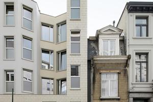 51N4E griffen die Typologien der bestehenden Fassaden auf und entwarfen in einer freieren Interpretation eine unregelmäßig gezackte und verputzte Straßenfassade, die sich durch Vor- und Rücksprünge auszeichnet und die die Gesamtlänge der Fassade auf einen kleineren Maßstab herunterbrechen soll