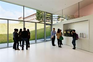 Mit einer breiten Glasfront öffnet sich der Campus in den Schlossgarten, der sich an dieser Stelle wie eine antike Theateranlage absenkt und den Studierenden einen grünen Außenraum schafft, der sich bis auf das begrünte und begehbare Dach ausdehnt