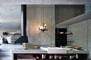 Die konstruktive Hülle zeigt sich innen als Sichtbetonfläche. Die Kücheneinbauten nehmen das Material wieder auf<br />