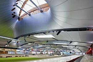 Eine besondere Rolle<br />kommt dem Dach zu. Es handelt sich um eine Fachwerkkonstruktion aus Holz und Stahl, die raumseitig<br />mit einem textilen Kälteschirm ausgerüstet<br />ist<br />