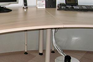 Systemboden mit Modulfliesen als Belag: rechts neben dem Tischbein ein Kabelanschluss in den Bodenhohlraum