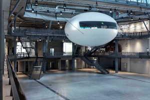"""In der dreigeschossigen """"Arena für Nachhaltigkeit"""" schwebt ein """"Cocoon"""", der über Brücken mit den einzelnen Ausstellungsebenen verbunden ist."""