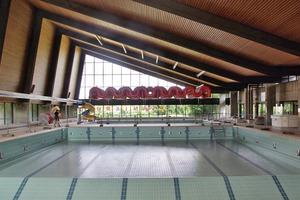 Die Schwimmhalle vor der Sanierung: Das Tageslicht wird von den dunklen Deckenflächen geschluckt, die nach der Sanierung hell und frisch erscheinen