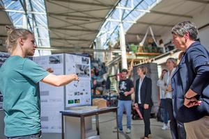Projektleiter Christian Brosig präsentiert Bundesbauministerin Dr. Barbara Hendricks Steckverbindungen, mit denen die Wandmodule verbunden werden