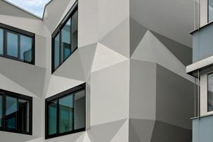In den fensterlosen Bereichen entwicklt die Fassade ihre Origamiqualität. Licht und Schatten geben ihr eine gefaltete papierneWirkung