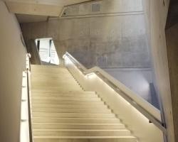 Treppe hinauf zum Aussichtsbalkon; Geschosse übergreifende Lufträume lassen Tageslicht über Betonwände hinunterfließen