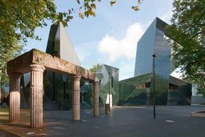 Blaugrün schimmert die Keramikfassade durch die Bäume der Mainzer Neustadt. Im Vordergrund erinnern Mauerreste an die alte, von den Nationalsozialisten zerstörte Synagoge<br />