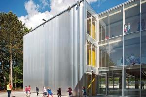 """<div class=""""9.6 Bildunterschrift"""">Die Trapezbleche der Fassade aus glänzendem Aluminium spielen mit dem Container-Zitat auf die temporäre Nutzung des Schulbaus an</div>"""
