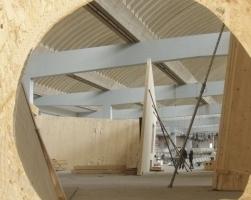 Blick in die Halle vom Eingang aus, die Bretterwand wird demnächst eine Glasfuge zwischen Bestand und Empfangsbauten