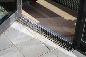 Detail: Schwellenfreier Hauseingang und Terrassenaustritt im Erdgeschoss mit vorgelagerter Rinne und Rostabdeckung in der Ausführung<br />
