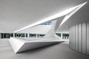 Im neu gestalteten Foyer erstreckt sich über drei Etagen eine spektakulär in unterschiedlichen Neigungen aufgefaltete, kristalline Raumskulptur