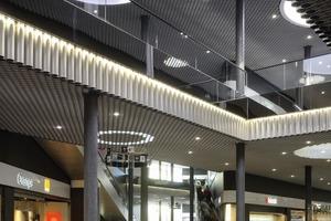 Die abgehängte Decke besteht aus silbrig glänzenden Aluminiumzylindern und bildet ein großes, richtungsloses Gewebe über mehr als 10000m² Fläche. Das Zylinderinnere wird durch LEDs angeleuchtet<br />