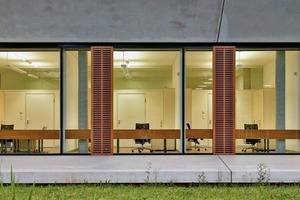 Ein trichterförmiger Betonrahmen umfasst die Glasfront, hinter der sich die Räumlichkeiten der Forscher befinden