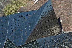 Für die Dachbekleidung wurden dreidimensionale Sonderformen kreiert. Als abstrahierende zeitgenössische Adaption von historischen Biberschwanzziegel entstanden konkave, konvexe und flache Keramikkacheln, die in einem grün-schwarzen Ton glasiert je nach Lichteinfall und Stand-punkt ständig wechselnde Dachimpressionen liefern<br />