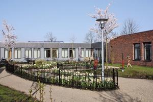 """<div class=""""4.1 Bildunterschrift"""">Die rotbraunen Klinker</div><div class=""""4.1 Bildunterschrift"""">fassaden und grauen Holzverschalungen erinnern ebenso an die typisch niederländischen Bautraditionen von Wohnvierteln, wie die niedrigen Gartenzäune um die Blumenbeete</div>"""