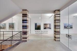 Große Glasflächen begrenzen die Ausstellungsräume zum Treppenhaus hin. So entstehen weite, lichte und trotzdem voneinander getrennte Räume