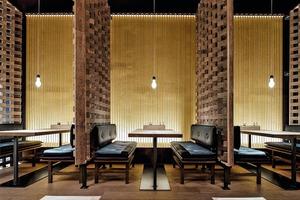 In den Separées wird die diffuse Beleuchtung aus den Wandelementen  nur durch eine abgependelte Licht- quelle über den Tischen akzentuiert