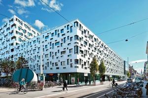 Sockelgeschoss mit Innenhof, darüber der Riegel mit weiteren Appartements (Ansicht von der Güterstraße)<br />