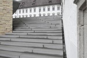 Links im Anschnitt die Ziegelfassade der neuen Bibliothek. Rechts und Mitte: Altbau. Die Treppe führt hinauf in den Garten, unter dem sich zweigeschossig das neue Archiv befindet