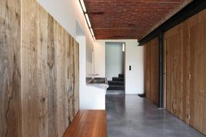 Auch bei der Materialwahl im Inneren griff Bart Lens auf einfache und lokal verfügbare Materialien zurück, wie dem sägerauen, unbehandelten Holz für die Zwischenwände, den Betonböden oder den weiß gestrichenen Wänden