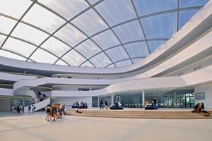 Raumgeometrien, Podeste und offene Galerien bestimmen das Gebäudeinnere. Die Halle wird von einem ETFE-Dach überspannt, dessen dreilagige Kissen permanent mit vorgetrockneter Luft befüllt werden