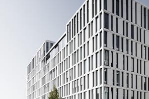 Die Entscheidung für eine Aluminium-Glas-Bandfassade hatte gegenüber der ursprünglichen Planung mit nichttragenden Betonfertigteil-Fassadenstützen den Vorteil, dass durch die hohe Maßgenauigkeit des Metallbaus eine sehr gute Basis für die Montage der Glasfaserbeton-Elemente gegeben war