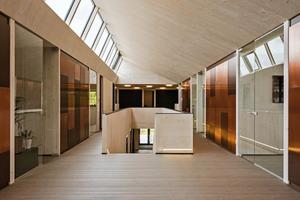 Tiefe Schranknischen aus Brettsperrholz – die gleichzeitig tragende Wände sind – verbergen diskret sensibles Aktenmaterial hinter kupferbeschlagenen Türen