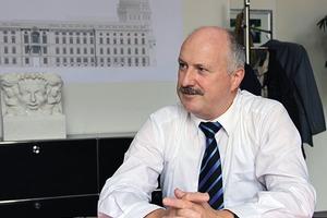 Hans-Dieter Hegner mit der DBZ im Gespräch. Deutlich im Hintergrund ablesbar das Humboldt-Forum, für das Hegner seit dem 1.5.2016 Vorstand Bau ist