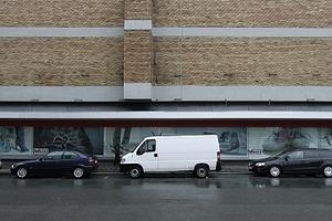 Vertikalen im Horizontalen: Der Erkeraufbau gliedert die geschlossene Wand und bringt (etwas) Tageslicht ins Innere. Unten Ladenflächen mit (hier geschlossenem) Schaufenster