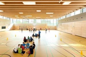 Die Zweifeldsporthalle im Erdgeschoss ist aufgrund der Topografie des Geländes teilweise in den Hang geschoben. Sie orientiert sich zum Lärmschutzwall hin