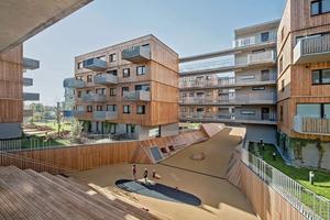 Die Gestaltung und die verwendeten Materialien lassen ein Ensemble entstehen: Die drei-, vier- bis sechsgeschossigen Wohnungsriegel variieren allein durch die versetzten Betonbalkone in ihrer Gestalt. Die Betonbalkone sowie die Holzfassaden sind vorgefertigte Elemente