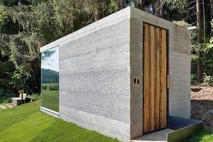 Beton, Holz und verspiegeltes Glas, das die Natur reflektiert.