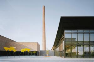 Das Auditorium rechts und das Kunden- und Besucherzentrum links. In der Mitte die Vergangenheit: der Hochkamin der ehemaligen Ziegelei
