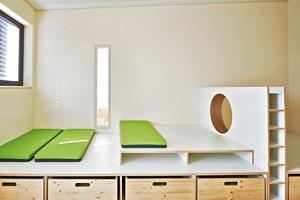 Auf begrenztem Raum erarbeiteten die Architekten platzsparende Lösungen: Ein Podest zum Spielen und Turnen wird, wenn die Kisten ausgezogen sind, zu Betten