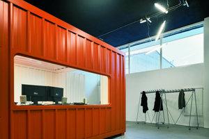 Drei größere Transportcontainer, wie zufällig abgestellt, zonieren den Raum in verschiedene Funktionsbereiche