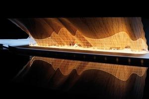 Die von ALA Architects entwickelte 3500 m² große, geschwungene Wave-Wall aus Eichenbrettern ragt 35 m aus und wird durch eine vertikale Glaswand in Vordach und Foyer unterteilt<br />