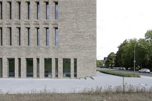 Der Viergeschosser hinter Ziegelkleid öffnet sich über eine tieflaibige Lochfassade zum Campus