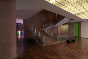 Lichtreflexe auf Wänden und der Glasfassade im zentralen Raum des 1. OG