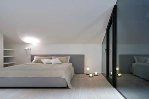 Im Dachgeschoss befinden sich zwei Schlafzimmer. Das eine bietet Ausblick auf den offenen Durchgang zum Pool in den Garten