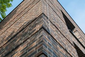 """<div class=""""13.6 Bildunterschrift"""">Der Architekt wählte für die Fassade den """"Original Wasserstrich Backstein Klinker""""von Hebrok in der Farbgebung """"terra"""". Der dunkle Stein ist dabei teilweise in Fußsortierung eingesetzt, sodass das Fassadenbild lebendiger wirkt. Dabei werden die sonst nicht sichtbaren Rückseiten der Steine, die produktionsbedingte Abdrücke haben, zur Fassadengestaltung genutzt</div>"""
