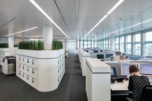 """Analog zum Ursprungskonzept kann durch die Anforderungen des Brandschutzes und der dadurch erfolgten Strukturierung der Büroebenen wieder größtmögliche Flexibilität in der Bürostruktur erreicht werden. """"Smart Working"""" nennt sich das mobile Bürokonzept, das auf sich verändernde Arbeitswelten, die immer mobiler und digitaler sind und verstärkt auf Teamarbeit hinauslaufen, ausgerichtet ist. Die Innenraumgestaltung, die sich aus den Gestaltungsprinzipien der Hülle mit abgerundeten Ecken ableitet und über eine reduzierte Farbgebung zoniert, folgt der zukunftsweisenden Arbeitswelt"""