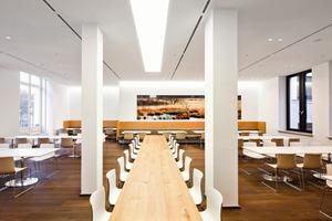 Etwas mehr Spielraum hatten die Architekten für die Gestaltung der Cafeteria, der Konferenzzonen oder der sich im Altbau befindlichen Kantine. Die entworfenen Möbel in der Cafeteria und in der Kantine offenbaren einen Blick fürs Detail: Kaffeemaschinen, Getränke-, Brötchen und Tablettausgabe sind in einemrechteckigen, orange bedrucktem Glas verkleideten Möbel untergebracht ,das nicht nur flächenbündig, sondern auch praktisch ist. Und die geschwungen-versetzten Ledermöbel bieten überraschend neue Gesprächsmöglichkeiten<br />