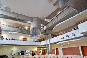 Die Gestaltung mit schallhartem Sichtbeton konnte hier, in der Aula eines Gymnasiums in Lünen, bewahrt, die Akustik aber gleichzeitig mit untergehängten, fugenlosen Akustikelementen verbessert werden