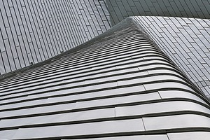 """<div class=""""4.1 Bildunterschrift"""">Für die Gebäudehülle wurde 0,8 mm starkes Titanzink von Rheinzink in der Oberflächenqualität vorbewittert<sup>pro</sup> blaugrau verwendet. Auf dem Dach wurde es in Doppelstehfalz- und an der Fassade in Winkelstehfalztechnik verlegt</div>"""
