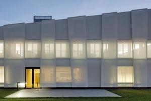 Das Gebäude hat eine Fassade aus Glasgewebe, die an weißes satiniertes Glas in erinnert. Die so eingehüllte Gebäudekubatur ist mit einer leichten hellgrauen Unterspannbahn bespannt. Der Grauton ist hier mit einer Nuance Blau abgetönt<br />