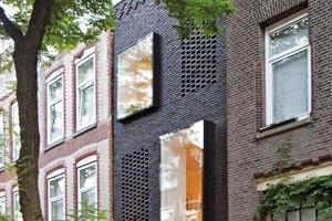 Tagsüber zeigen sich an der Straßenfassade nur zwei Erkerfenster. Erst abends, wenn im Haus die Lichter angehen, werden drei weitere Fenster hinter dem offenen Mauerwerksverbund sichtbar