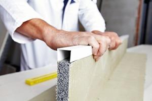 Einen bauphysikalisch sicheren und optisch einwandfreien Übergang zwischen Laibungsdämmplatte und Fensterrahmen gewährleistet bei der Rigitherm-Lösung das ThermoProfil. Die U-förmige Kunststoffleiste wird auf die Außenkante der Platte gesteckt, die später den Fensterrahmen berührt<br />